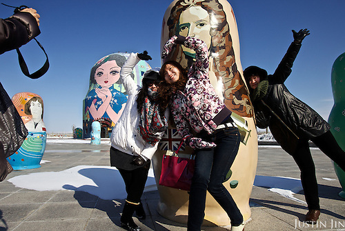 "Chinese tourists pose for a picture in front of giant Russian ""Matryoshka"" dolls in Manzhouli, a Chinese boomtown on the China-Russia border. The town has grown from a smaller village just two decades ago to a town of 200,000 people, and its economy is driven by trade with Russia across the border."