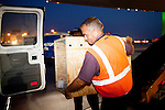 A team lifts a crated puppy that was unloaded out of cargo from a Delta 777 flight from Johannesburg, South Africa to unload crated pets at Gate F8 outside of the Maynard H. Jackson Jr. International Terminal at Hartsfield–Jackson Atlanta International Airport, in Atlanta, Georgia on August 28, 2013.