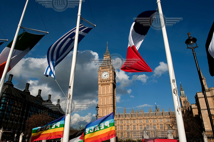 Greek and French flags fly in front of The House of Commons and The Clock Tower in Westminster, London. Although the tower is popularly referred to as Big Ben, this is actually the nickname of the bell housed within whose official name is the Great Bell.