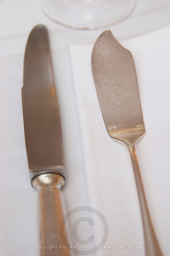 A silverware knife and fish knife on a white linen table cloth and napkin at the gastronomic restaurant Maceo in Paris