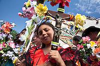 Francia, Camargue, Saintes Maries de la mer: la festa gitana in onore di Santa Sara la Nera, che si tiene ogni anno il 24 e 25 maggio. Il rituale prevede il trasporto della statua della santa dal mare alla terraferma e poi festeggiamenti con canti e balli. Nell'immagine: una bambina in mezzo ad altre persone mentre porta in mano un crocefisso addobbato con dei fiori e degli elastici colorati.<br /> feast of the Gypsies, May 25 veneration of Saint Sarah the black Saintes Maries de la Mer, Camargue, a