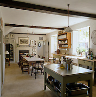 The large farmhouse kitchen has a rustic refectory table and is bathed in sunshine