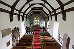 Raised angle view looking east down the nave towards the altar and east window with wooden pews, simple wood roof beams, whitewashed walls, interior of village parish church at Friston, Suffolk, England, UK. Mounted on the wall is a large Stuart Royal Coat of Arms of King James 1st 1605
