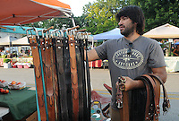 NWA Democrat-Gazette/FLIP PUTTHOFF<br /> LEATHER WORKS<br /> Armando Lopez sets up his booth Saturday morning August 8 2015 at the Bentonville Farmers Market in downtown Bentonville. Lopez makes belts and other leather items.
