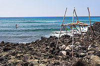 An altar stands inside the Ku'emanu Heiau with surfers in the background, Kahalu'u Bay, Kailua-Kona, Big Island.