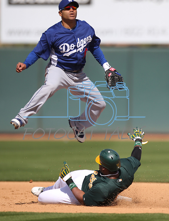 Dodgers shortstop Jerry Hairston leaps over A's baserunner Brandon Allen turning a double play during a Cactus League preseason game between the Dodgers and the A's in Scottsdale, Ariz., on Wednesday, March 7, 2012. The game ended 3-3..Photo by Cathleen Allison