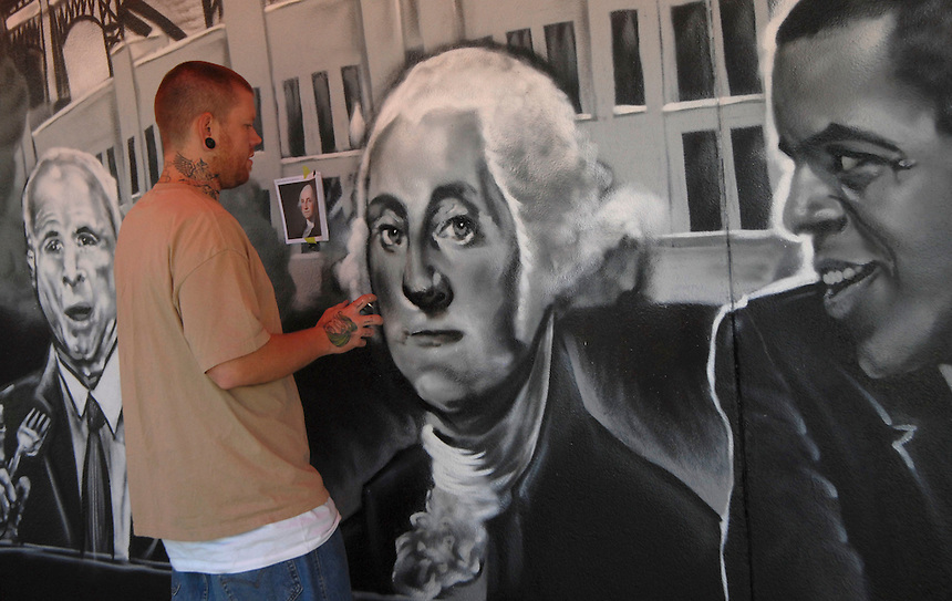 14 August 08: Denver artist Adam Moorhead spray paints the likeness of George Washington on August 14, 2008. In advance of the 2008 Democratic National Convention, local artists create a mural featuring past, current, and future local, national, and world leaders, on the side of a local business, Snooze, in Denver, Colorado. According to a Snooze employee, the work is a collaboration of the Colorado Democratic Party, the Cuty of Denver, and Snooze, a breakfast restaurant in Lower Downtown Denver (LoDo). The mural features the likenesses of John McCain, George Washington, Barack Obama, Thomsa Jefferson, Denver mayor John Hickenlooper, and the Dalai Lama, together at a single breakfast table.
