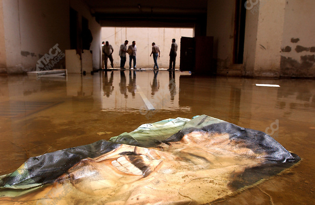 Former inmates of the Al-Hakemiya Secret Service interrogation centre in Baghdad searched the building as a strip of a Saddam Hussein portrait lay in the flooded courtyard. April 19, 2003