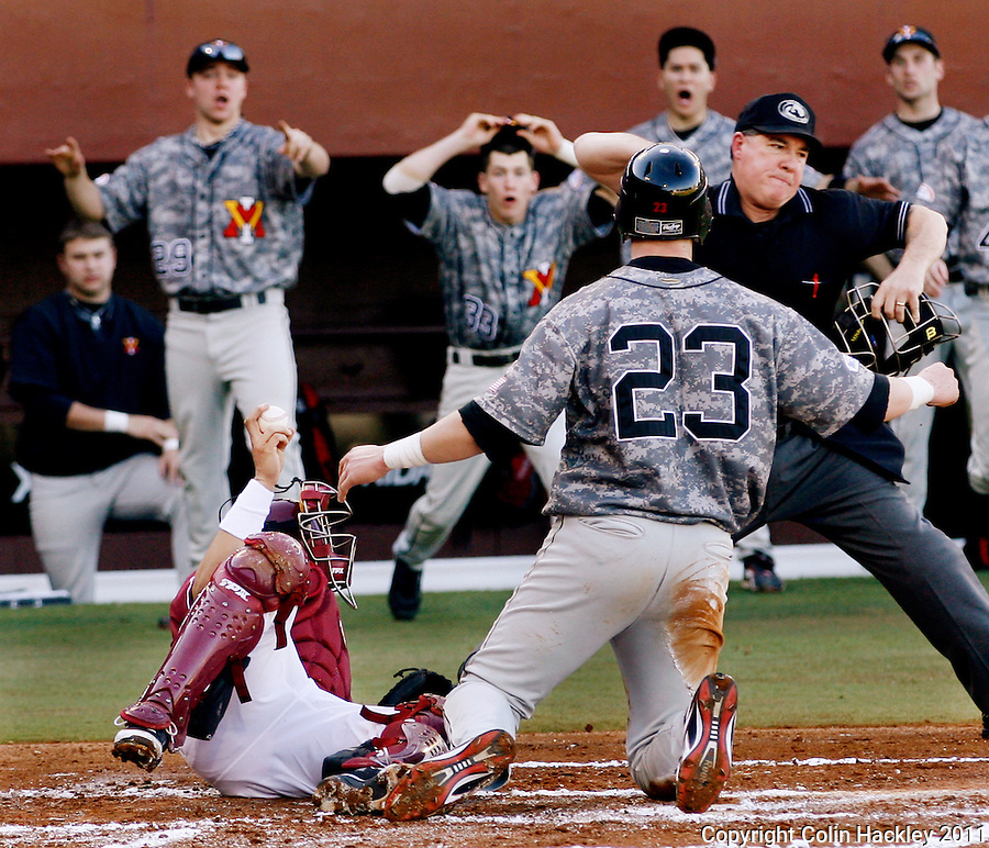 TALLAHASSEE, FL 2/18/11-FSU-VMI BASE11 CH-Florida State catcher Rafael Lopez holds the ball up as Home Plate umpire Bruce Ravan calls the out on Virginia Military Institute's Graham Sullivan during first inning action Friday at Dick Howser Stadium in Tallahassee The Seminoles beat the Keydets 12-0 in the season opener for both teams..COLIN HACKLEY PHOTO