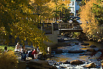 Folks enjoy the river and fall color on a late afternoon in September, near the Fall River in Tregent Park at the west end of downtown, Estes Park, Colorado, Rocky Mountains