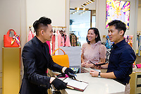 HONG KONG - MAY 04: Patricia Szeto and Jonathan Lui shop for a handbag in a fashion store in IFC (International Finance Center) shopping mall in Central business district, on May 4, in Hong Kong. (Photo by Lucas Schifres/Pictobank)