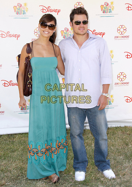 "VANESSA MINNILLO & NICK LACHEY.The 20th annual ""A Time for Heroes"" Celebrity Carnival benefiting Elizabeth Glaser Pediatric AIDS Foundation held at Wadsworth Theater on the Veteran Administration Lawn in West Los Angeles, California, USA. .June 7th, 2009.full length blue dress teal long maxi couple jeans denim sunglasses shades purple shirt .CAP/DVS                                                  .©Debbie VanStory/Capital Pictures."
