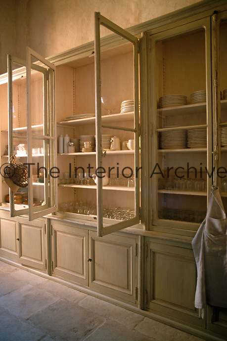 In this spacious kitchen a series of elegant built-in glass-fronted cabinets houses an impressive collection of glassware and crockery
