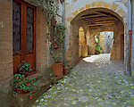 Tuscany, Italy: Morning sun streams through an arched passage to the cobbled street in the ancient village of Sorano in southern Tuscany, Grossetto