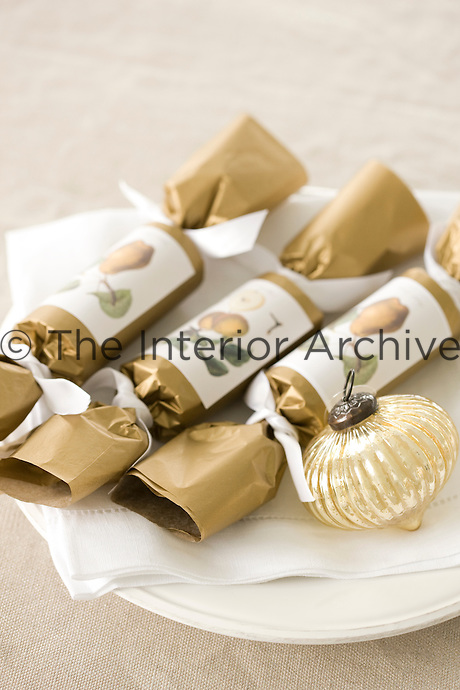 Three Christmas crackers and a gold bauble on a plate