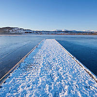 Snow covered jetty and winter ice on Llangorse lake, Brecon Beacons national park, Wales