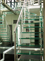 A custom staircase of steel and reinforced glass leads from the ground floor to the downstairs dining room and kitchen; the flooring is polished slate. A mirrored wall creates a wonderful sense of space.