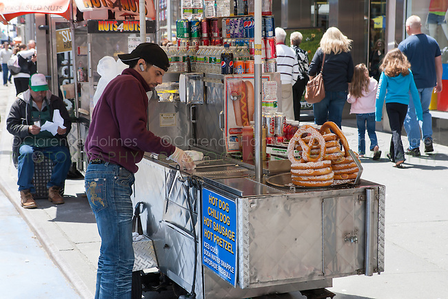 A street vendor works from his cart selling hot dogs and other food in Times Square in New York City