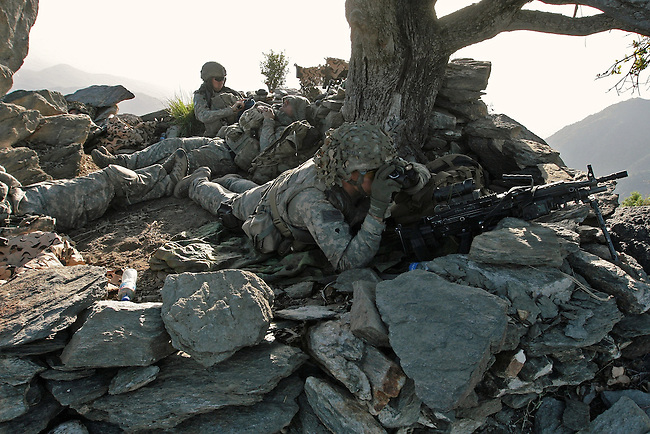 Spc. Stan Thomas, 21, of Palm Desert, Calif., a soldier with Company A, 2nd Battalion, 503rd Infantry Regiment, uses binoculars to scan for Taliban fighters from atop a mountain in the Narang valley, in Kunar province, Afghanistan. The soldiers were protecting a team during a two-day mission that directed air and artillery strikes on Taliban positions in the valley below. May 17, 2008. DREW BROWN/STARS AND STRIPES
