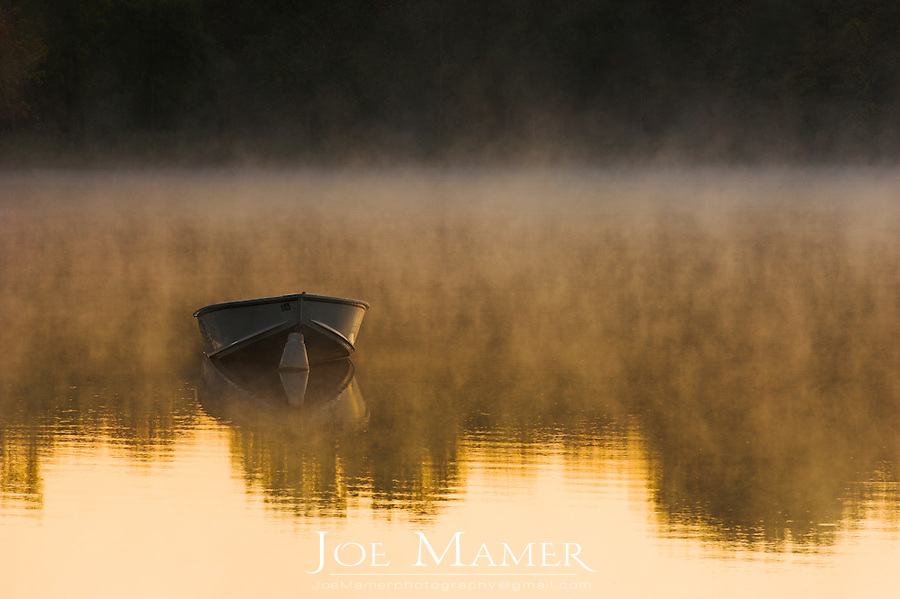 An aluminum row boat moored offshore on a lake at sunrise with fog rising off the lake and trees reflected on the waters surface.