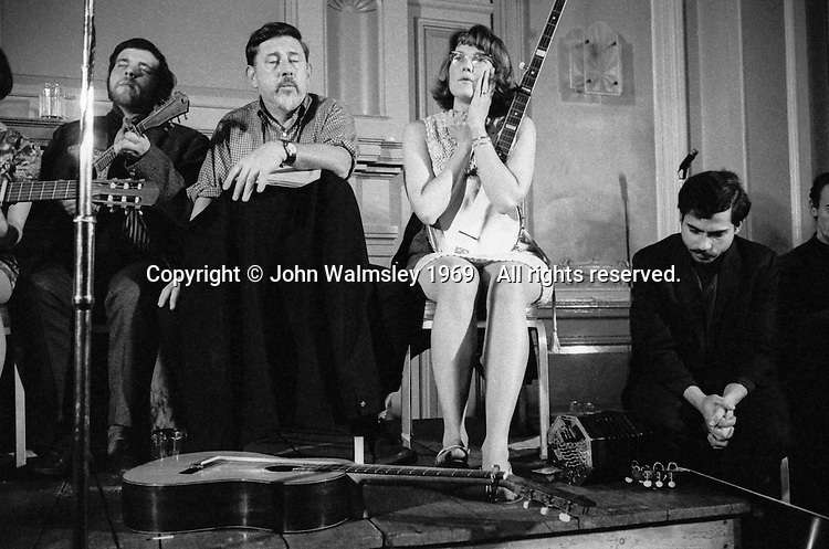 Ewan MacColl (second from the left), singer, song writer, dramatist, playright, political activist (real name, Jimmie Miller) and Peggy Seeger, song writer and performer (and member of the North American Seeger folk family) at a folk club in London around the late 1960s.  If you can identify the venue, please let me know.