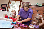 August 7, 2010. Hillsborough, North Carolina.. Christine Green teaches 2 of her grandchildren how to sew at her home in Hillsborough.. Ms. Green grows many fruits and vegetables, has goats and cows and produces at home a large part of the food her family consumes.