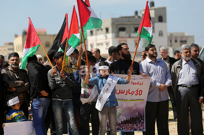 "Palestinians hold placards and the national flags during a rally against ""Deal of the Century"" and to announce the launch of the great return march near the border with Israel in east of Gaza city on March 17, 2018. Photo by Ashraf Amra"