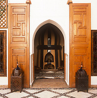 The entrance to the Zamzam Riad hotel giving a view into an entrance hall with a fireplace and zebra skin rug.