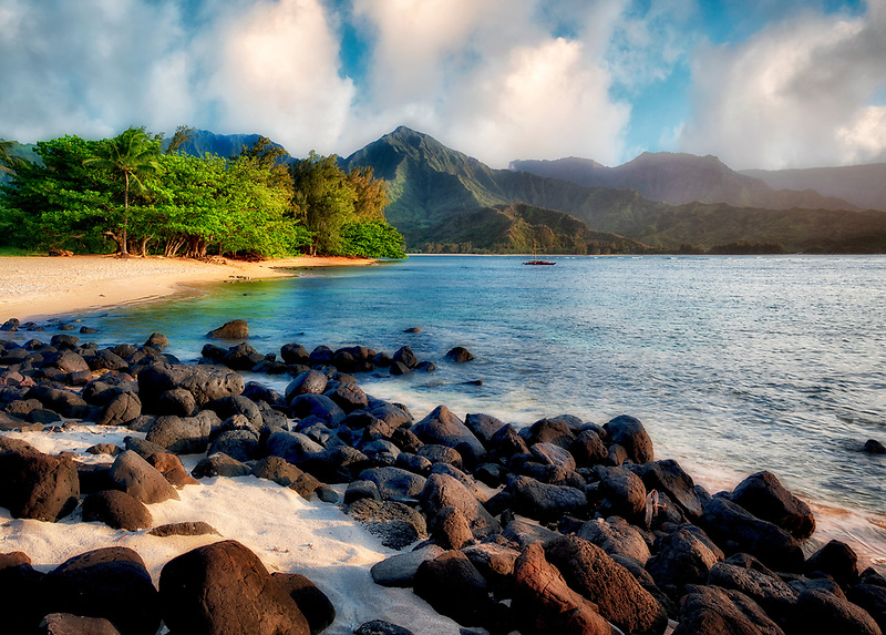 Hanalei Bay with white sand and black volcanic rocks. Kauai, Hawaii.