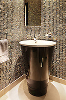 An unusual conical shaped pedestal wash basin in a bathroom clad with iridescent brown, grey and black mosaic tiles