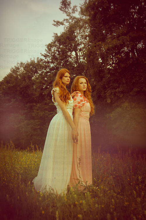 Two girl in pastel gown standing outsdoors in spring and holding hands