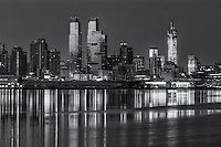 Buildings on the West Side of Manhattan, from  approximately 54th Street to just south of the Intrepid Sea, Air and Space Museum, and their reflections on the Hudson River during the last hour before sunrise.  Space Shuttle Enterprise is visible on the deck of the Intrepid (courtesy of hurricane Sandy) and One World Trade Center (Freedom Tower) is visible in the background.  The prominent twin towers are the Silver Towers.