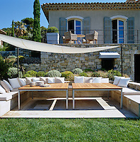 A simple canvas stretched between poles provides shade over a banquette fashioned out of an old stone wall