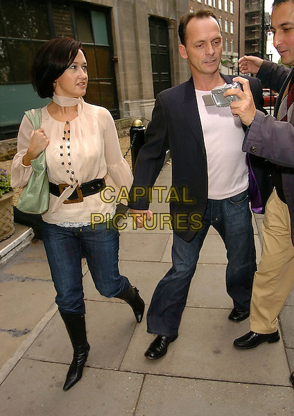 ANGELA LONSDALE & PERRY FENWICK.Tribute to Wendy Richard MBE luncheon, Grosvenor House, London, UK..October 30th, 2005.Ref: CAN.full length jeans denim holding hands camera cream blouse.www.capitalpictures.com.sales@capitalpictures.com.©Capital Pictures