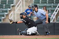 Kannapolis Intimidators catcher Daniel Gonzalez (23) sets a target as home plate umpire Justin Anderson looks on during the game against the Greenville Drive at Intimidators Stadium on June 7, 2016 in Kannapolis, North Carolina.  The Drive defeated the Intimidators 5-2 in game two of a double header.  (Brian Westerholt/Four Seam Images)