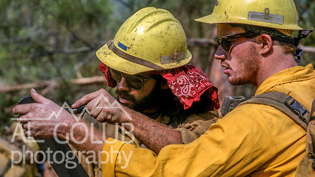 September 3, 1987 Pine Mountain Lake, California --Stanislaus Complex Fire -- Stanislaus National Forest firefighters Phil Hope and Rob Laeng work on chainsaw bar. The Stanislaus Complex Fire consumed 28 structures and 145,980 acres.  One US Forest Service firefighter, David Ross Erickson, died from a tree-felling accident.