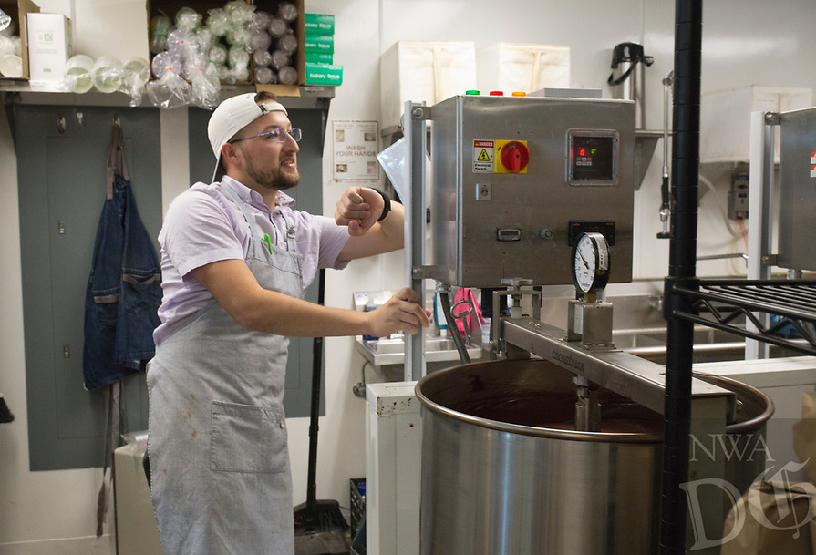 NWA Democrat-Gazette/CHARLIE KAIJO Bar Manager Michael Day checks on a melanger used to refine chocolate, Saturday, July 6, 2019 at Markham & Fitz Chocolate in Bentonville. <br /> <br /> Markham & Fitz Chocolate held a World Chocolate Day event showcasing chocolate samples from around the world.