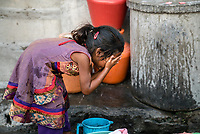 A young girl washes her face with municipal water in Ambedkar Nagar in Medak, Telangana, India.