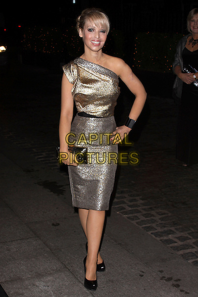 KATIE  PIPER  .At the Inspirational Women Of The Year Awards, Marriott Hotel, Grosvenor Square, London, England, UK, November 23rd 2010..full length gold silver one shoulder metallic dress hand on hip shoes clutch bag black bracelet cuff .CAP/AH.©Adam Houghton/Capital Pictures.