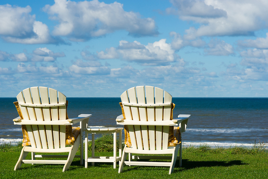 two chairs on a meadow with a view on the sea