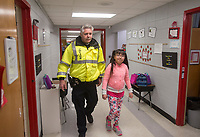 NWA Democrat-Gazette/BEN GOFF @NWABENGOFF<br /> Ashley Herrera, a 4th grade student, walks with Randy Harvey, Lowell police chief, Friday, March 9, 2018, at Lowell Elementary. Harvey acts as crossing guard at the school before spending time visiting with staff and students each morning.