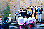 The Wine Route in early spring in Beaujolais, France. The village of Oingt, located in the southern part of the appellation.  Pictured here is a Fete de Conscrit.  These celebrations happen annually throughout the Beaujolais region.  All the people born in the same year and by extension to all those whose age ends with the same number.  (2013, 2003, 1993, etc…)  The color of the ribbons worn by the people represent the age (20's, 30's, etc…). Teenagers and children under the age of 16 wear pink (girls) or blue (boys).