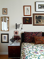 The bedroom has a retro feel with the richly embroidered cushions on the bed, a crewel bedspread bought from a thrift shop and the vintage wall light over the bedside chest of drawers; the walls are painted in Donald Kaufman Color's DKC-43.