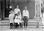Cora and Alonzo (Lon) Thomas operated a small grocery from the front room of this house at 715 C Street. Four of their five children are portrayed here. Baby Lonnie, born in 1909, sits on Herschel's lap. Agnes stands at left, and eldest son Wendell stands at the center. The young man at right is probably Lucius Knight, their mother's half brother. Wendell worked a typical variety of jobs in Lincoln--waiter, clerk, porter, laborer, and janitor--before founding the Thomas Funeral Home in Omaha. The Thomas family and many other African American families lived in the South Bottoms, a neighborhood mainly of Germans from Russia, Lincoln's largest immigrant group. The little blonde girl who leans into the right edge of this view serves as a reminder that Lincoln's residential neighborhoods were not segregated by race in the early 20th century--poor people of many ethnicities lived together. A few years later and through the middle third of that century, residential segregation became prevalent in Lincoln. A close-knit black neighborhood arose from that adversity, centered around Twenty-first and T Streets.<br />