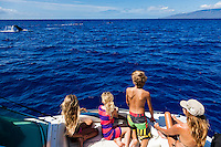 A family observes as swim close to their boat off of Maui.