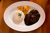 Oaxaca; Mexico; North America.  Lunch.  Turkey Breast in Black Mole Sauce with Rice and Sauteed Bananas.  Casa Oaxaca Restaurant.