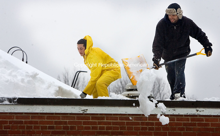 PROSPECT, CT. 11 February 2013-021113SV02-From left. Eric Figueroa and Jonathan Morreno of Green Construction work to shovel a 5-foot snowdrift from the top of Community School in Prospect Monday. Towns were worried about the heavy snow load due the combination of this weekend's storm, Mondays rain and two more storms predicted this week..Steven Valenti Republican-American