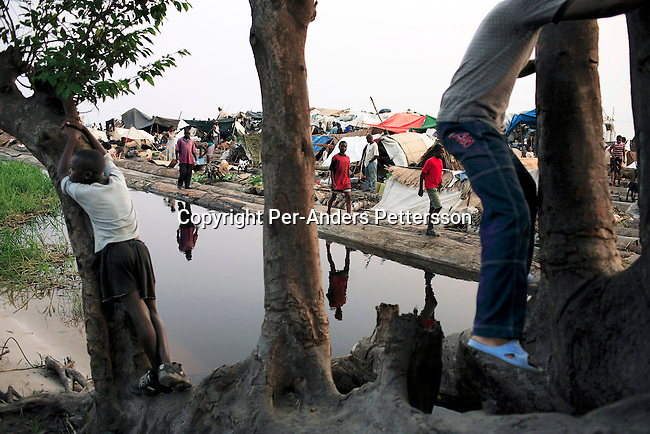 MBANDAKA, DEMOCRATIC REPUBLIC OF CONGO JUNE 30: Unidentified passengers relax on the Congo River shore as they travel on a boat made of big trees on the Congo River on June 30, 2006 outside Mbandaka, Congo, DRC. The boat traveled with about 150 passengers from Bumba to Kinshasa, a journey of about 1300 kilometers. The Congo River is a lifeline for millions of people, who depend on it for transport and trade. Passengers slept in the open, with their goats, pigs and other animals. Boat travel is the only option for most people along the river as there?s no roads or infrastructure. Very few can afford to fly in a plane to the capital Kinshasa. During the Mobuto era, big boats run by the state company ONATRA dominated the river. These boats had cabins and restaurants etc. All the boats are now private and are mainly barges that transport goods. The crews sell tickets to passengers who travel in very bad conditions. The conditions on the boats often resemble conditions in a refugee camp. Congo is planning to hold general elections by July 2006, the first democratic elections in forty years. The Congolese and the international community are hoping that Congo will finally have piece and the country will be rebuilt. (Photo by Per-Anders Pettersson)..