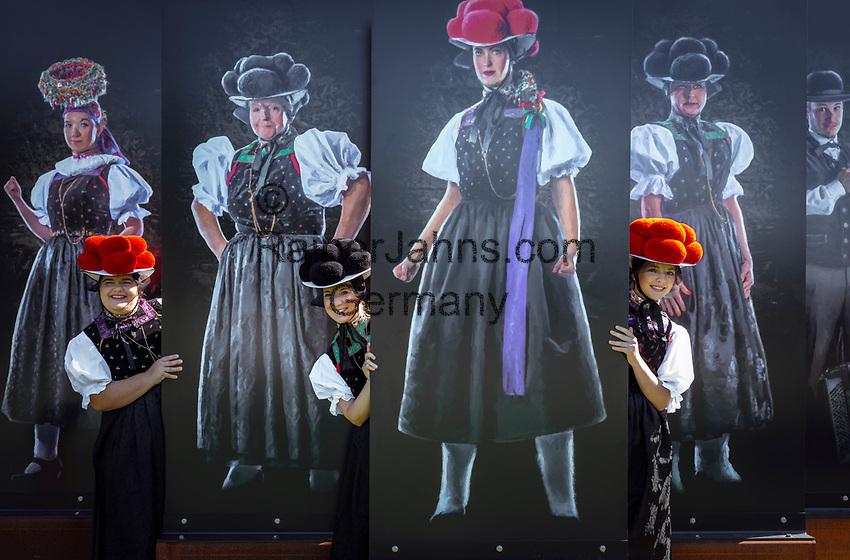 """Germany, Baden-Wurttemberg, Kirnbach (Wolfach): three young women posing in famous Black Forest costume with red and black Bollenhat in front of 'The Original' an installation by Jochen Scherzinger   Deutschland, Baden-Wuerttemberg, Ortenaukreis, Kirnbach (Wolfach): drei junge Frauen posieren in der beruehmten Kirnbacher Tracht mit dem roten und schwarzen Bollenhut, die heute in der ganzen Welt als Schwarzwaelder Tracht bekannt ist. In der Naehe des Startpunktes zum """" Kirnbacher Bollenhut-Talwegle"""" steht """"Das Orginal"""", eine Installation von Jochen Scherzinger"""