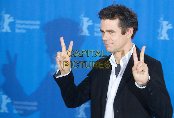 "TOM TYKWER.Photocall for ""The International"" during the Berlinale 2009, 59th International Berlin Film Festival, Berlin, Germany..February 5th 2009.half length black suit jacket hands v peace sign .CAP/PPG/JH.©Jens Hartmann/People Picture/Capital Pictures"